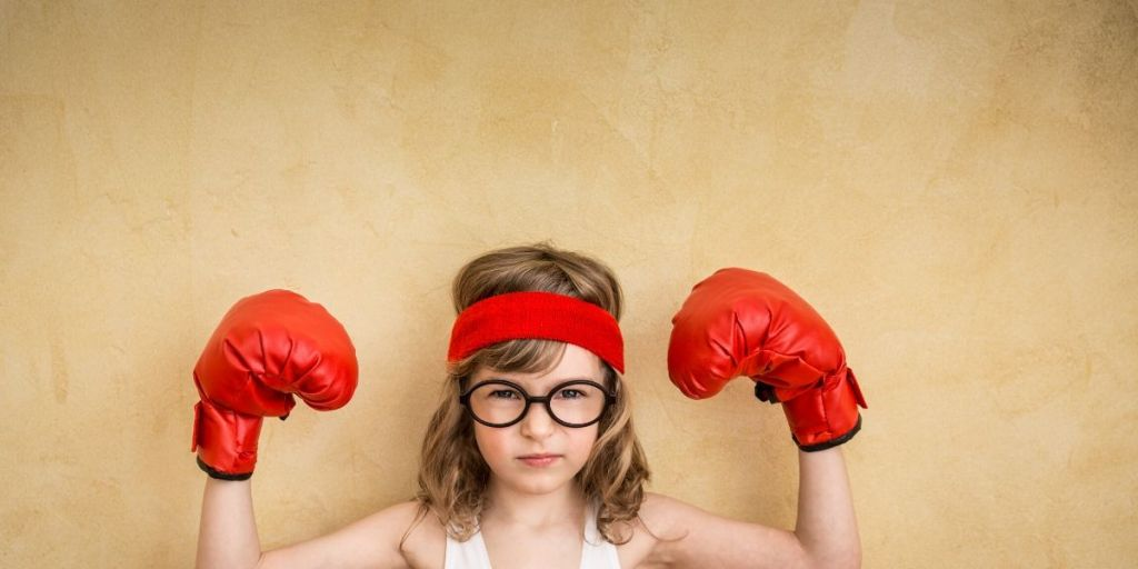 Child wearing boxing gloves and sweat band looking fierce