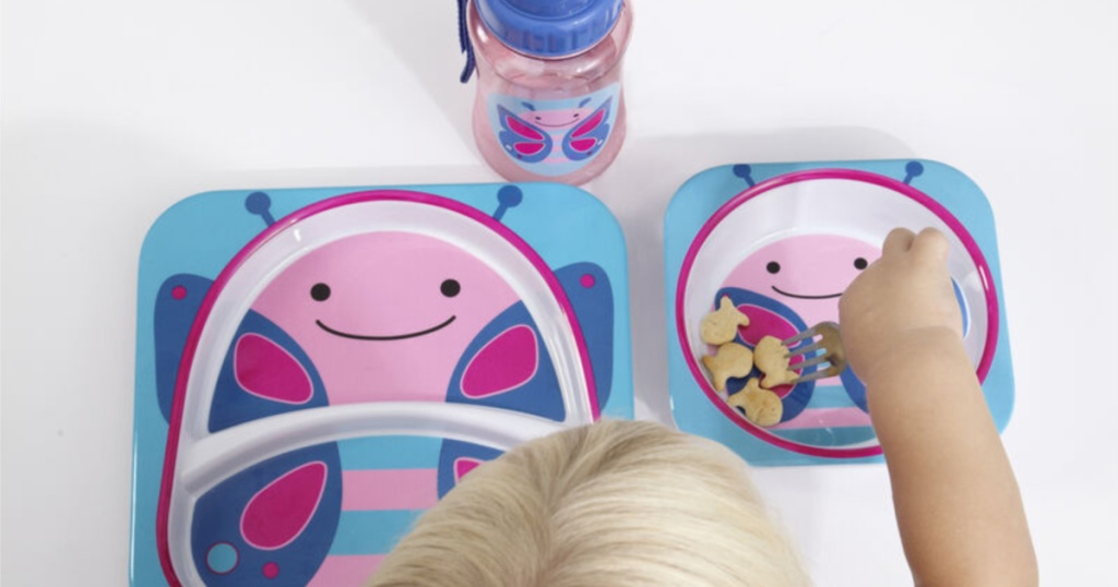 blonde child sitting in front of multi-colored butterfly designed plate, bowl, and sippy cup