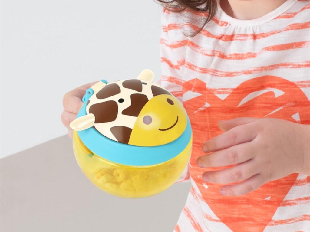 little girl holding yellow giraffe snack cup