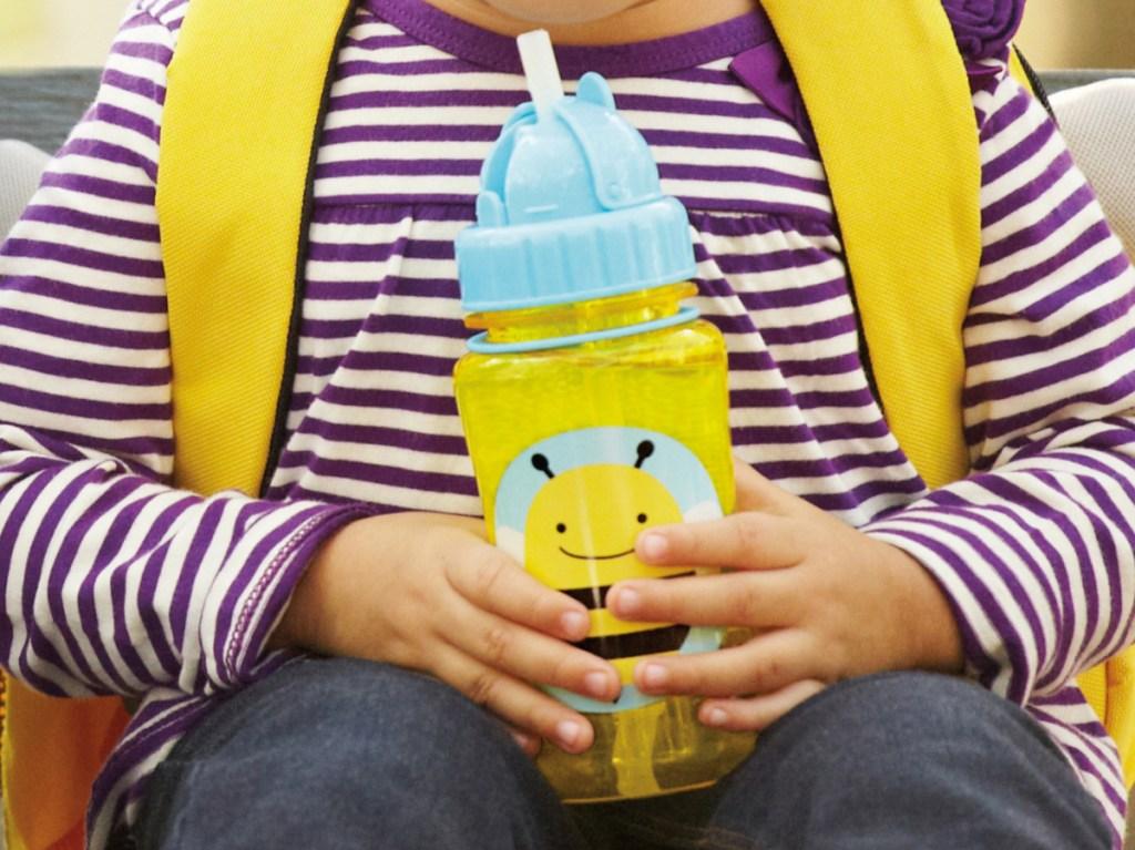 little girl holding yellow bee bottle