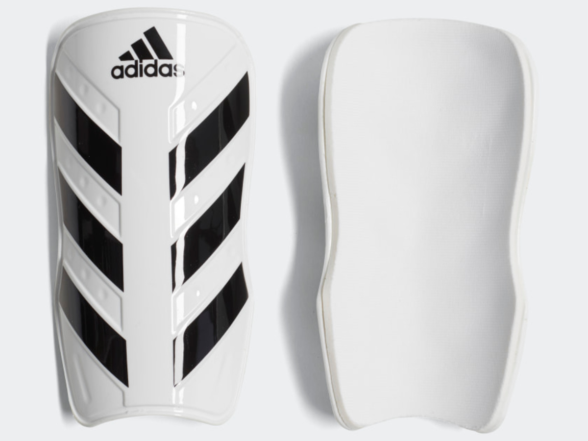 front and back view of white and black adidas shin guards