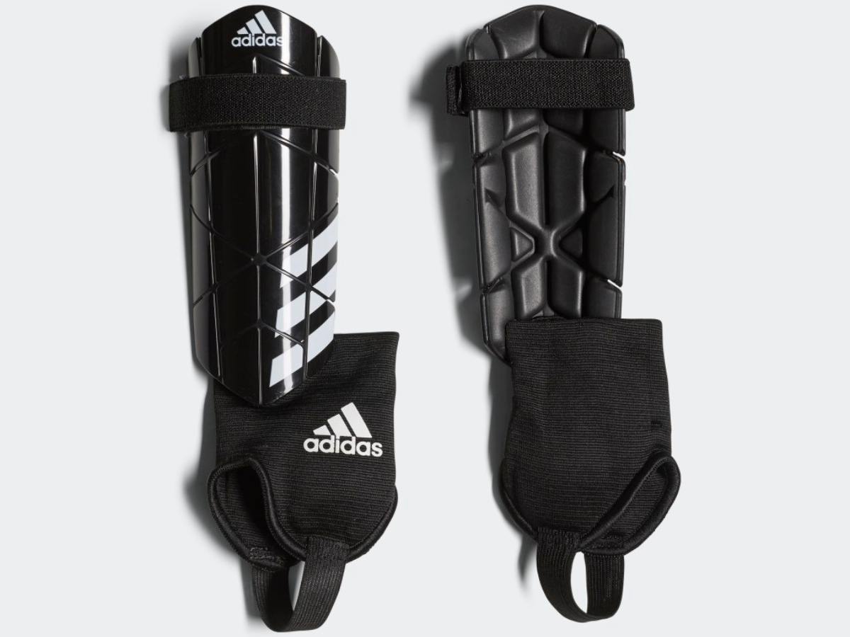 front and back view of black and white adidas shin guards