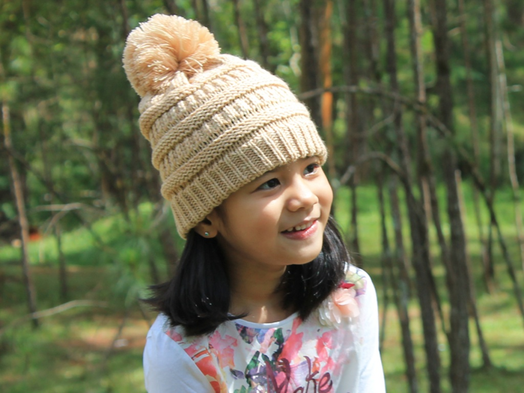 kid wearing tan beanie with woods in background