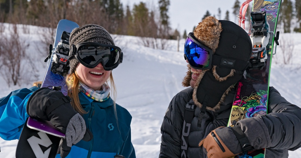 woman and man wearing goggles holding snowboards in snow