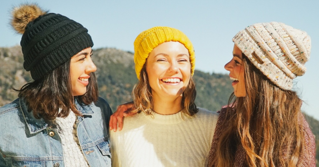 women wearing beanies outdoors smiling