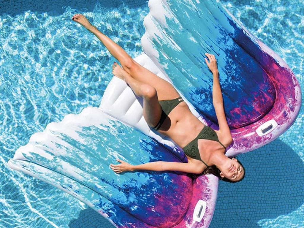 woman laying on an Intex Blue & Fushcia Ombré Wings Pool Float