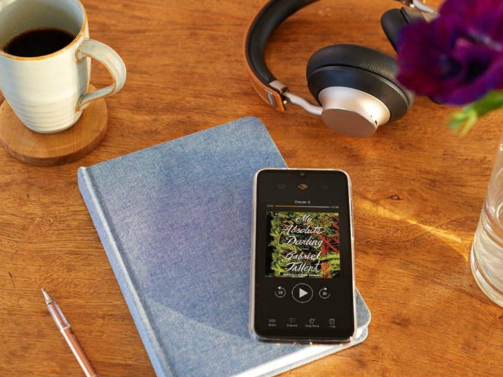 book on table with phone, headphones and coffee