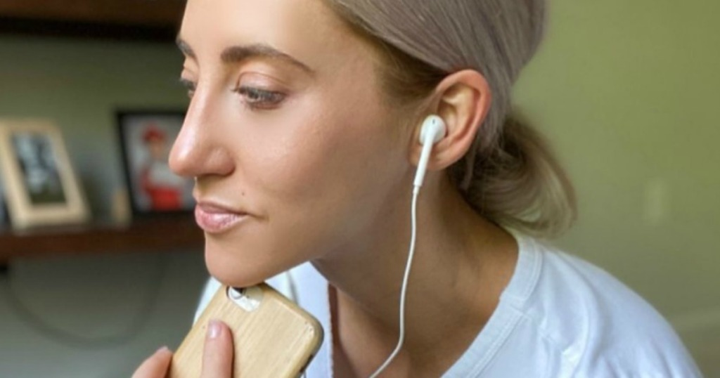 woman wearing headphones and a phone by bookcase