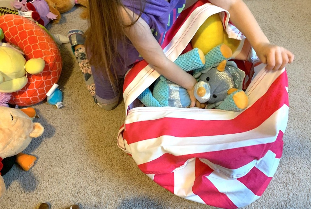 girl putting stuffed animals into hot pink and white stripe bean bag chair
