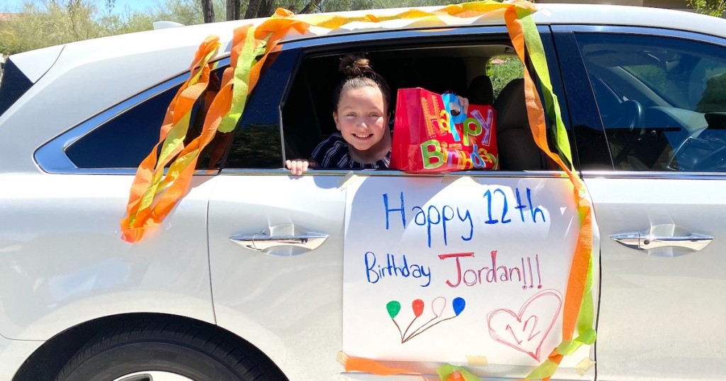 girl sitting in silver car with happy birthday poster on side with colorful streamers