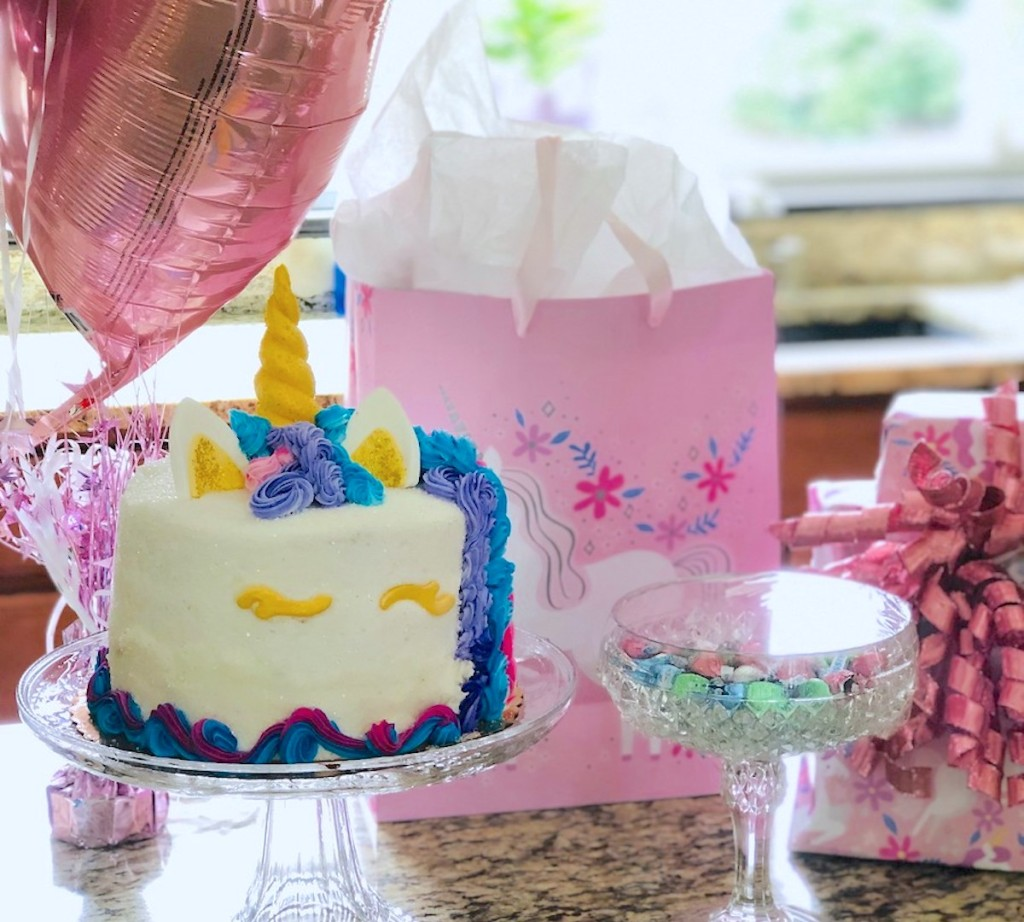 unicorn cake on glass stand with pink balloons and presents
