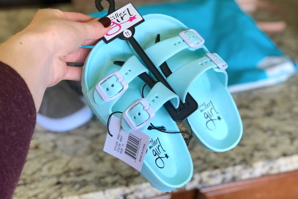 hand holding a pair of blue and white kids sandals on black hanger