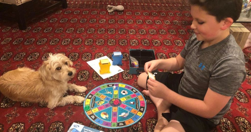 boy and dog playing board game on red carpet floor