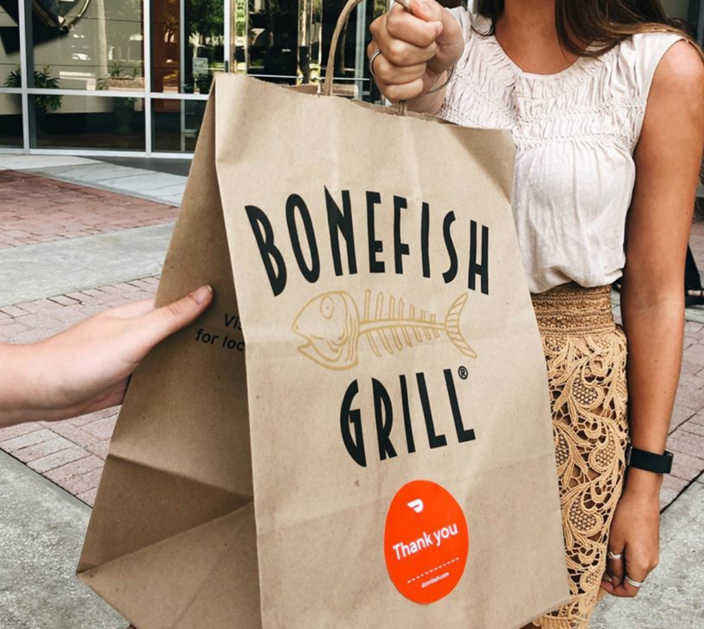 woman holding food delivery bag from bonefish grill restaurant deals