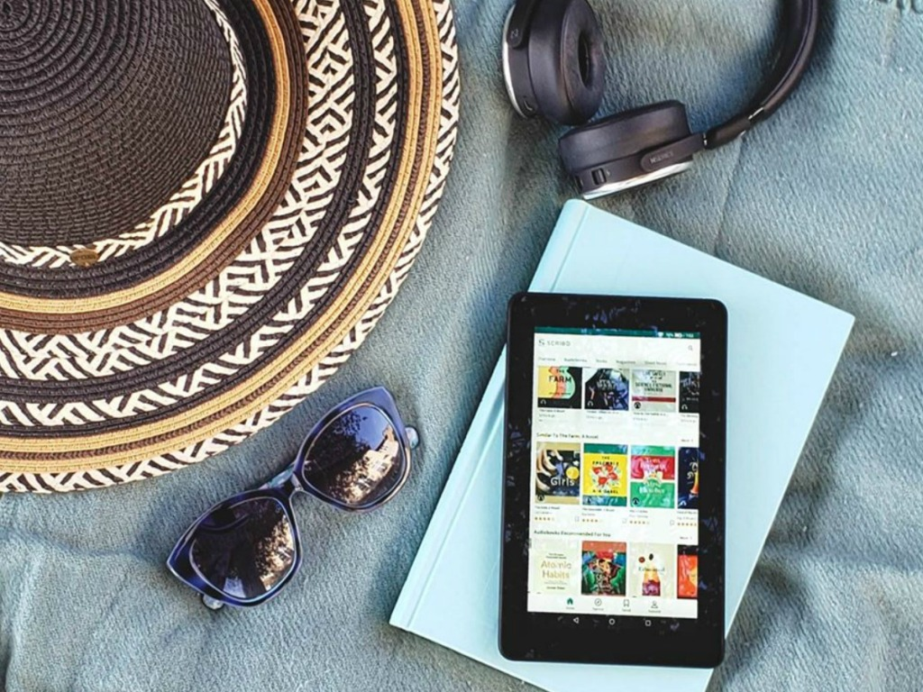 tablet, book, headphones, hate and sunglasses on blanket outdoors