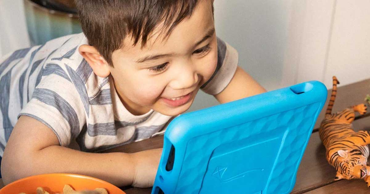 Boy smiling and looking at a tablet