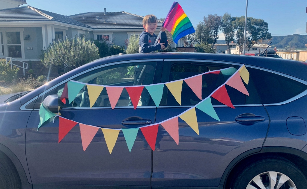 boy standing out of car holding rainbow flag