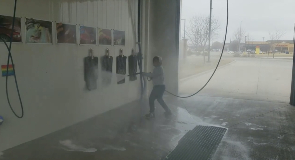 kid holding a hose at car wash with car mats hanging up on wall