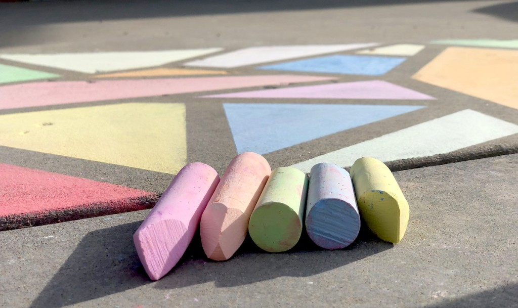various colors of sidewalk chalk laying in front of stained glass painted art on sidewalk