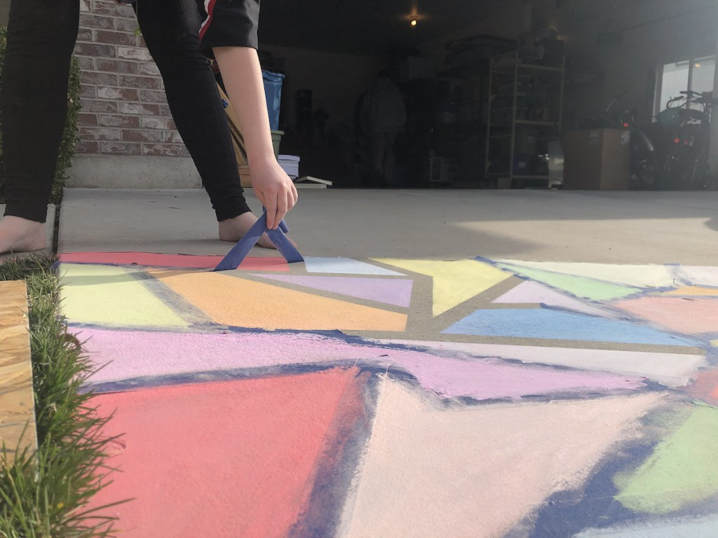 hand pulling blue painters tape of chalk colored pavement