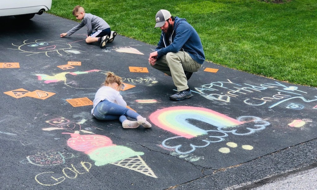 man and kids writing with chalk on driveway
