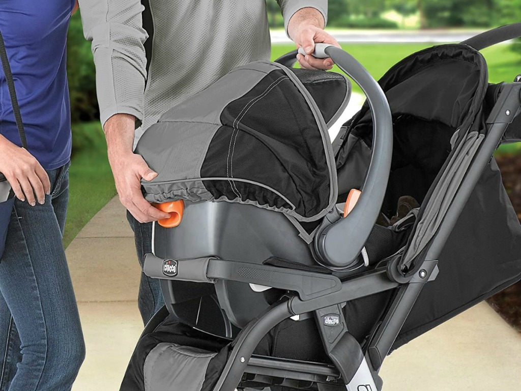 man and woman putting a carseat on the top of a stroller