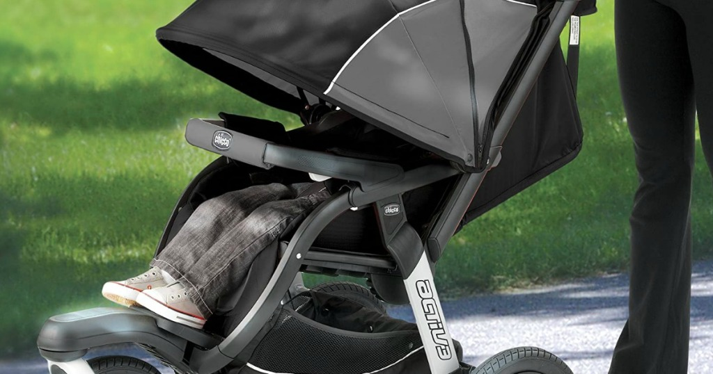 person pushing a black stroller with a child in it
