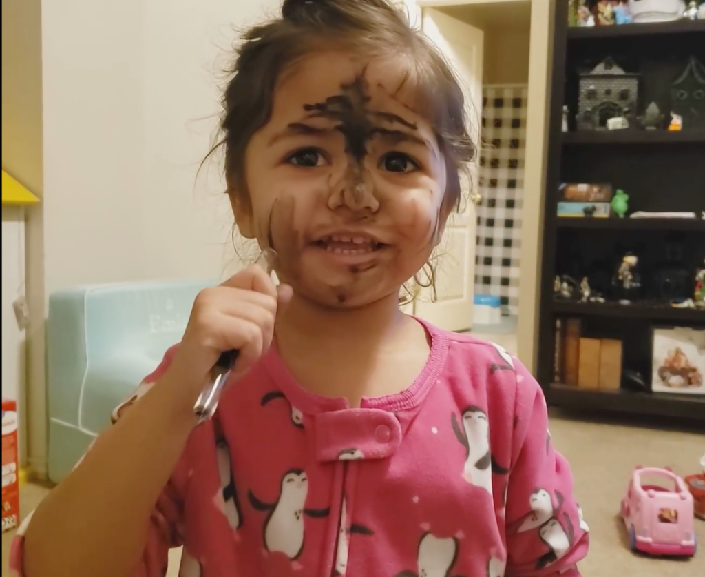 toddler girl with black makeup all over face