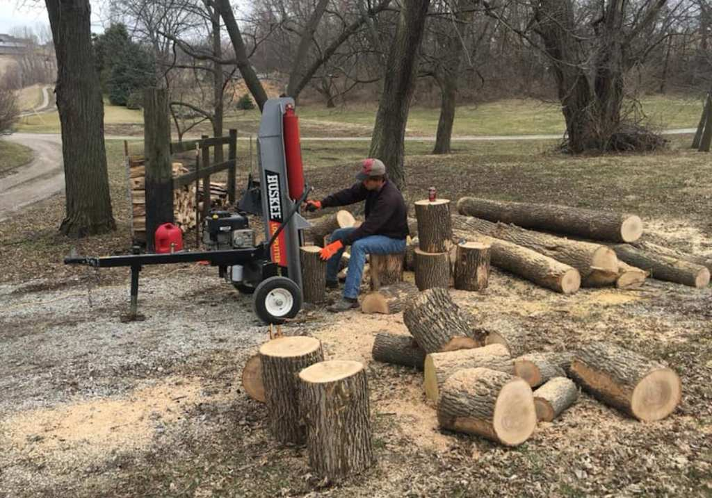 teen boy chopping tree stumps and wood in woods