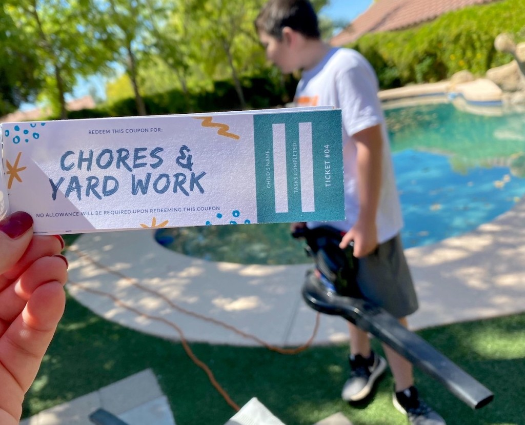 hand holding a chores and yard work coupon with kid holding leaf blower in background