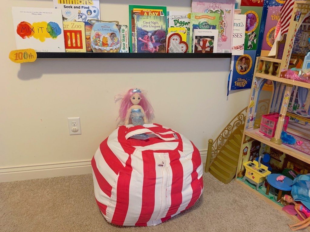clean kids room with hot pink and white stripe bean bag chair and various kids books