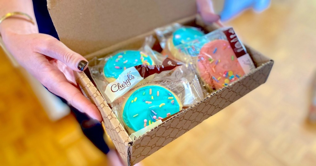 gifts under 10 - hands holding a cardboard box full of blue and pink sugar cookies