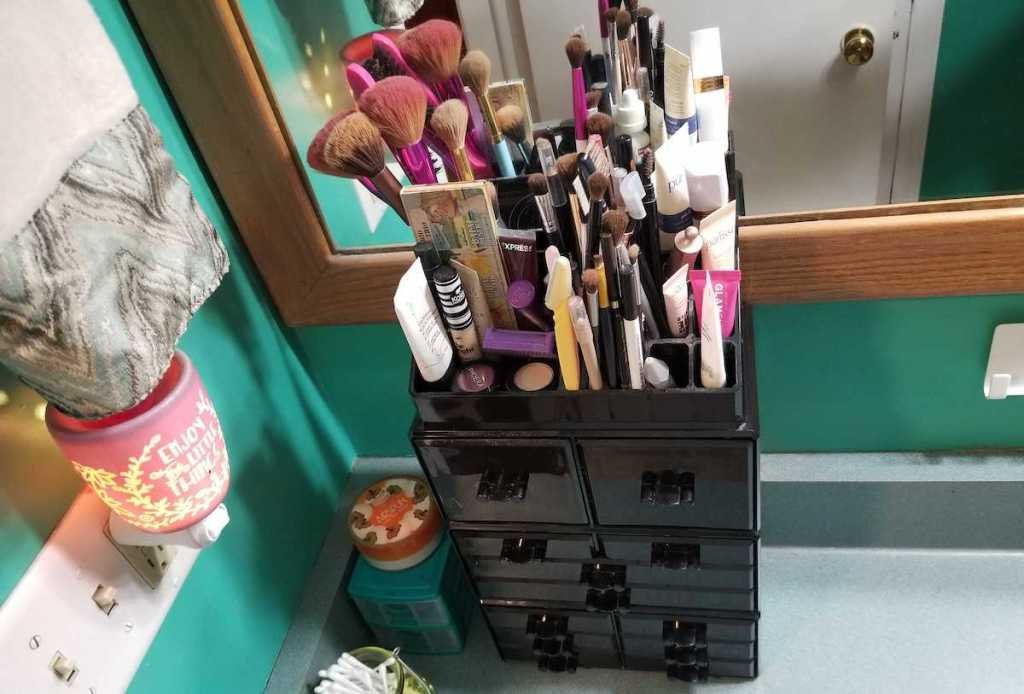 Various cosmetics and make up brushes in black tiered drawer organizer