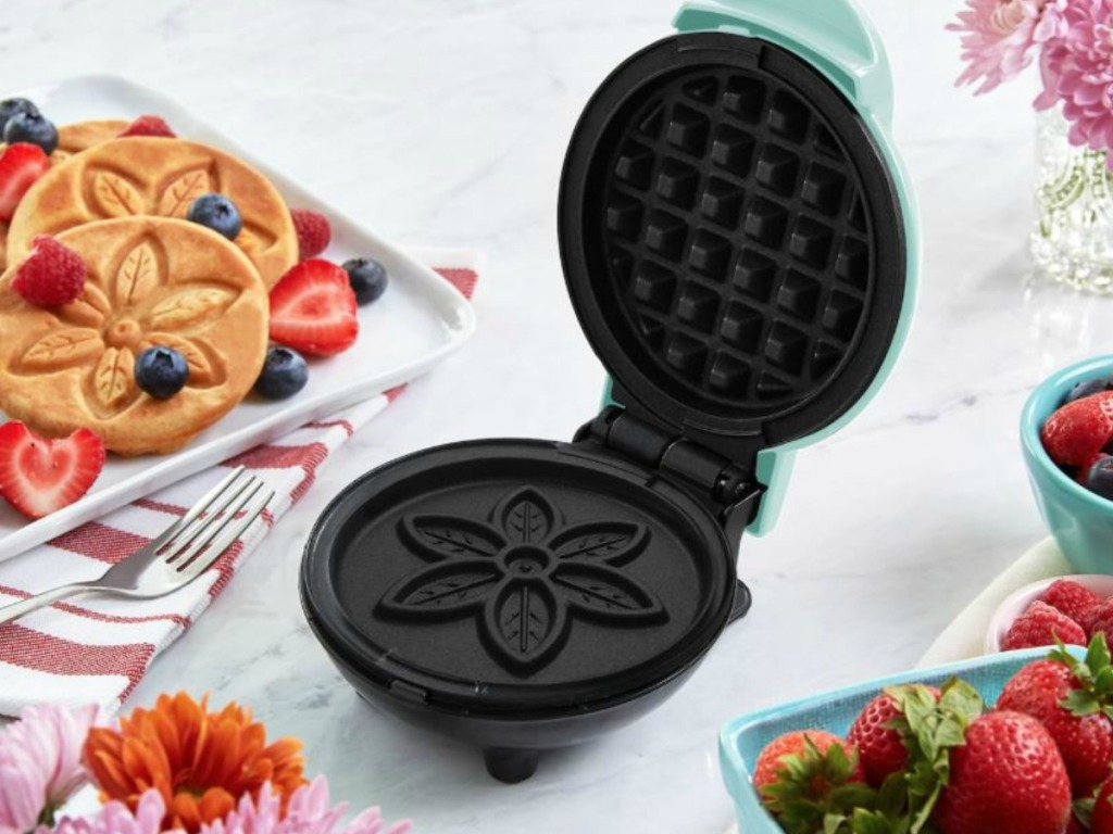 small waffle maker surrounded by strawberries on counter