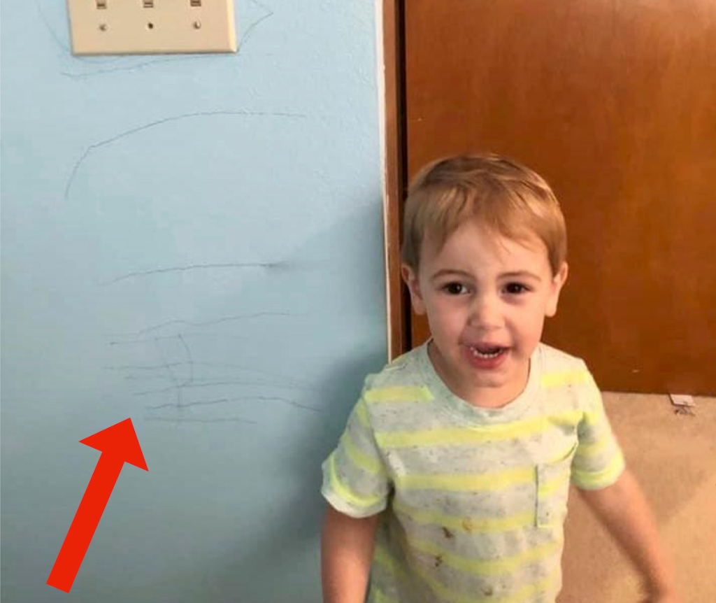toddler boy standing in front of blue wall with red arrow pointing to scratches