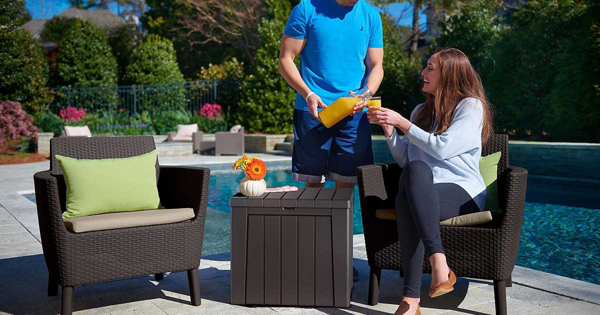 couple on a pool deck with chairs and a storage box