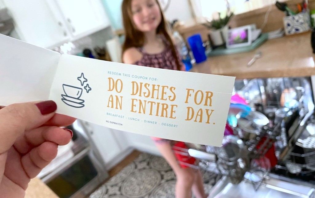 hand holding a mother's day coupon book in front of dishwasher