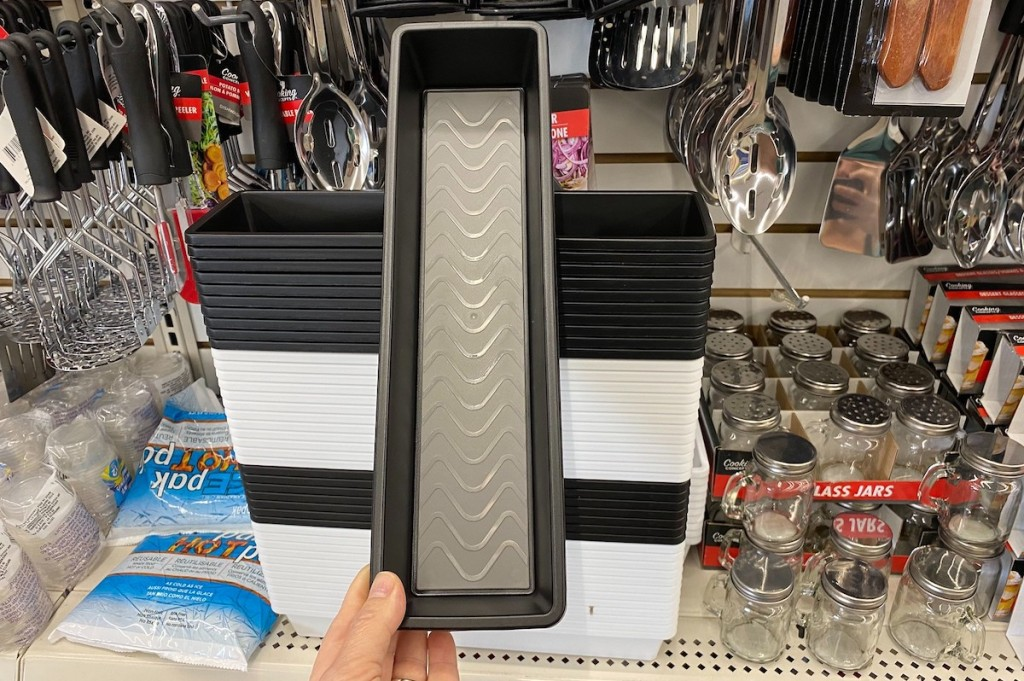 hand holding a black and gray drawer organizer