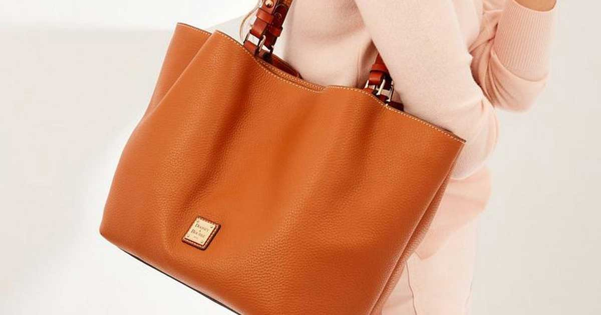 dooney and bourke purse on shoulder of woman