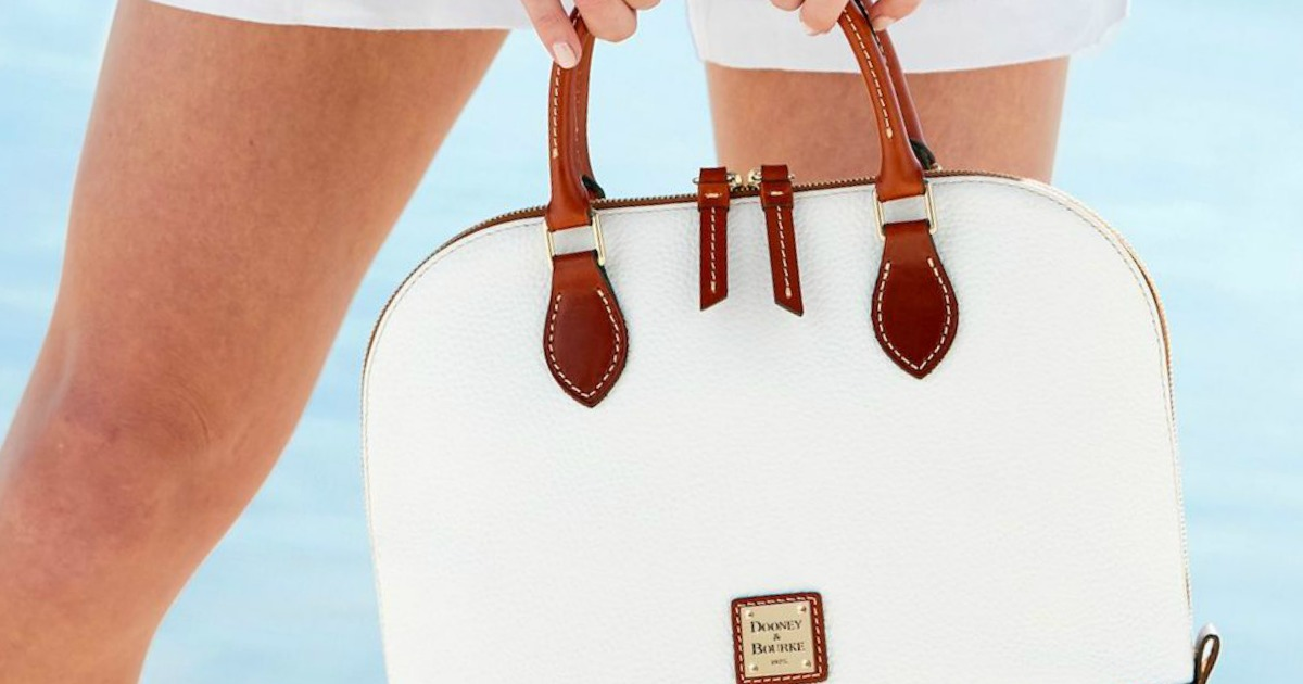 woman holding white leather purse