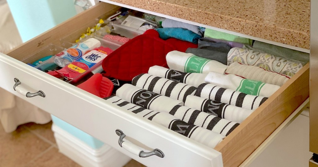 wide drawer with folded white and black towels with other various kitchen items