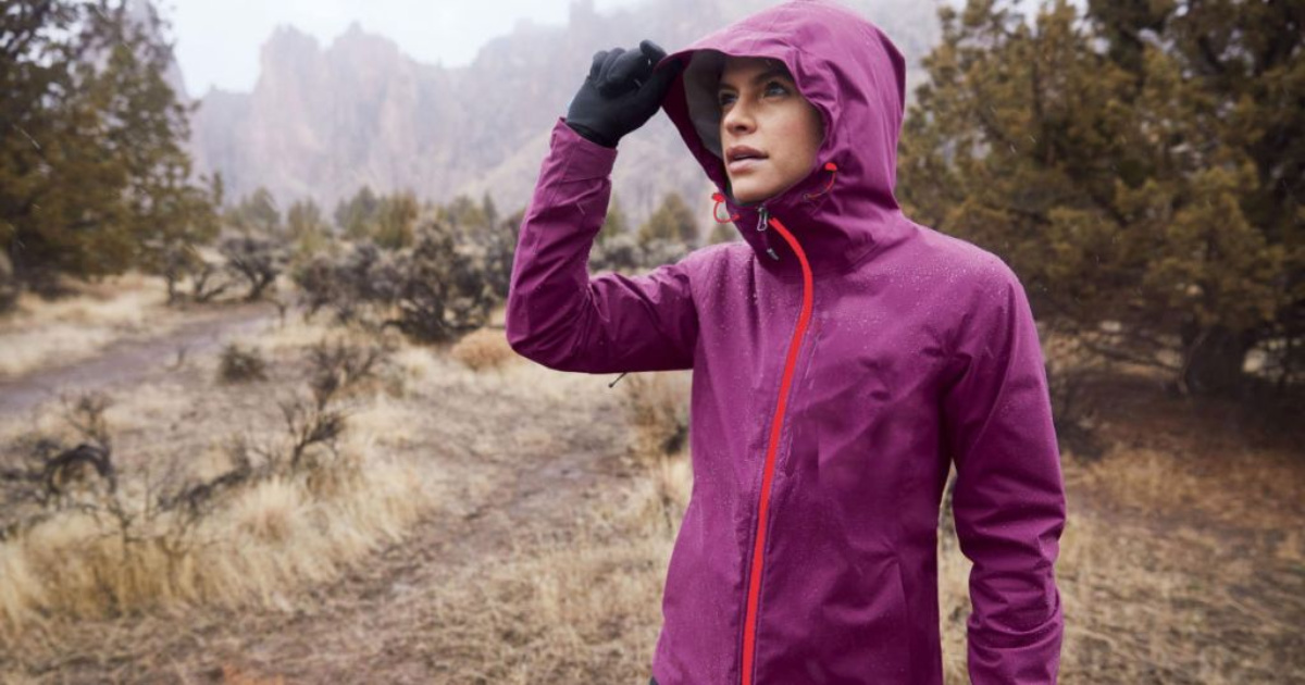 woman wearing a purple rain jacket outside with her hood up