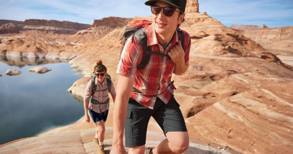 man and woman hiking mountains wearing shorts and button up shirts
