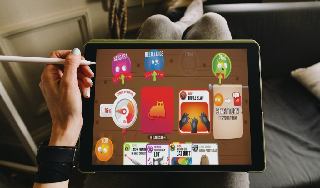 person holding stylist pencil with ipad on lap and feet up with exploding kittens game on screen