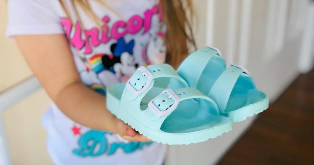 toddler holding blue sandals in hands