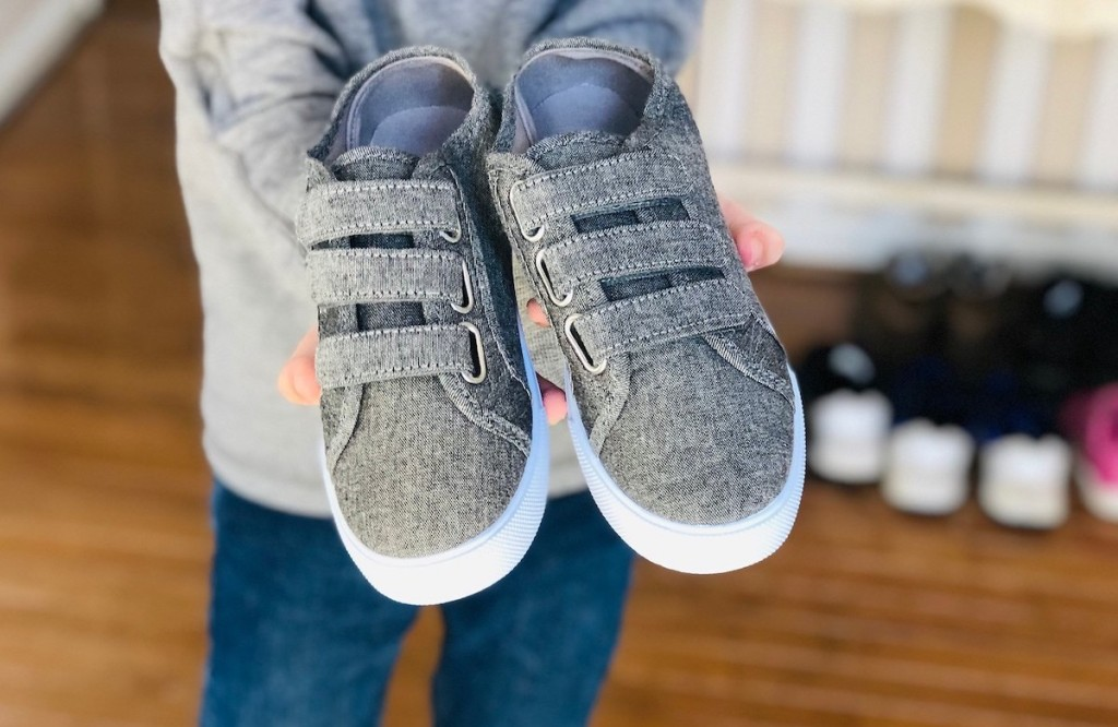 kid holding pair of gray triple velcro shoes