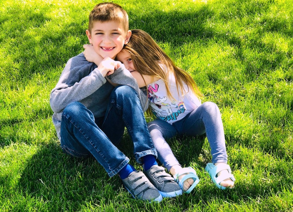 boy and girl hugging and smiling in green grass