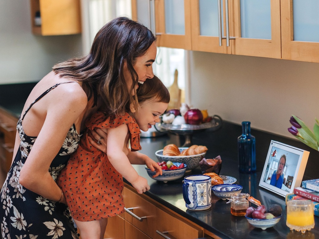 woman holding up toddler to see Facebook portal