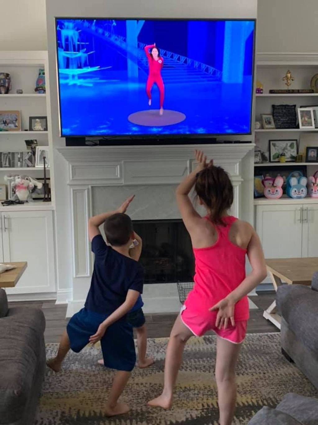 kids standing and posing in front of tv hanging over fireplace