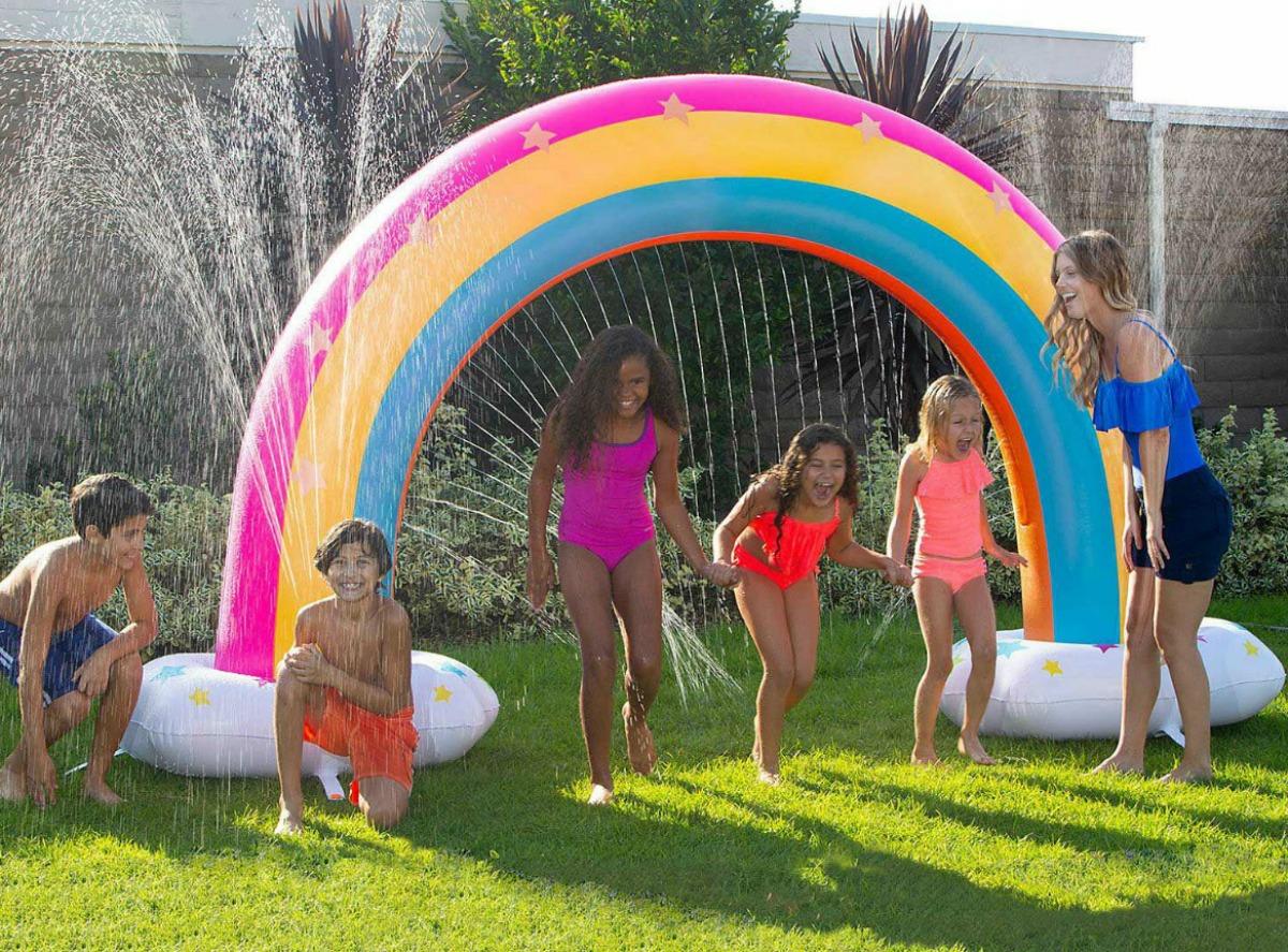 kids playing around a giant rainbow sprinkler